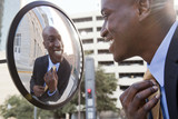 African American businessman adjusting tie in mirror