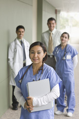 """Hispanic doctor, surgeons and administrator in hospital corridor"""