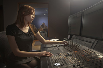 Caucasian woman working at audio control panel