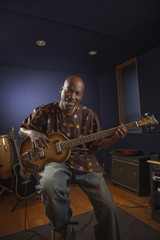 African American man playing guitar in studio