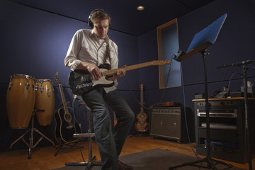Caucasian man playing guitar in studio