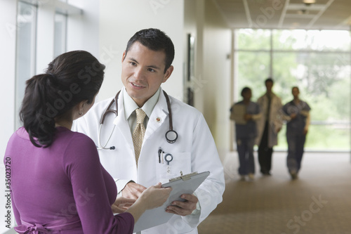 Hispanic doctor talking to co-worker in hospital corridor