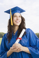 Mixed race woman wearing graduation cap and gown holding diploma
