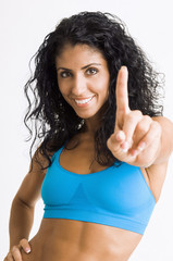 Mixed race woman in sportswear making Number One gesture