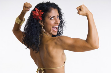 Mixed race woman body builder flexing muscles