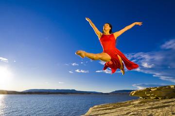 Hispanic woman dancing near lake