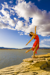 Hispanic woman dancing near lake