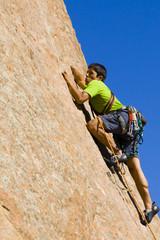 Hispanic man rock climbing