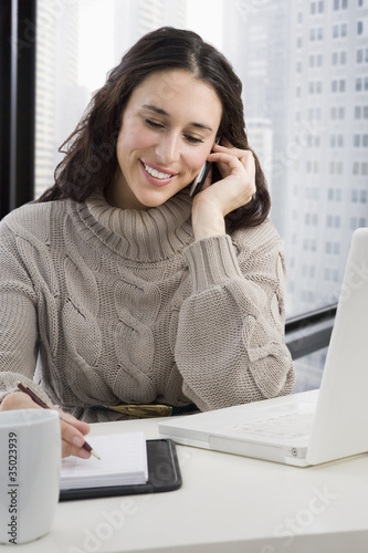Mixed race businesswoman talking on cell phone at desk