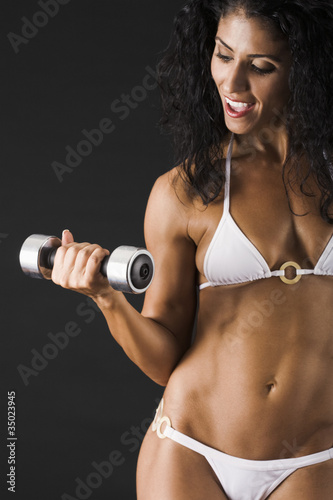 Mixed race female body builder doing biceps curls