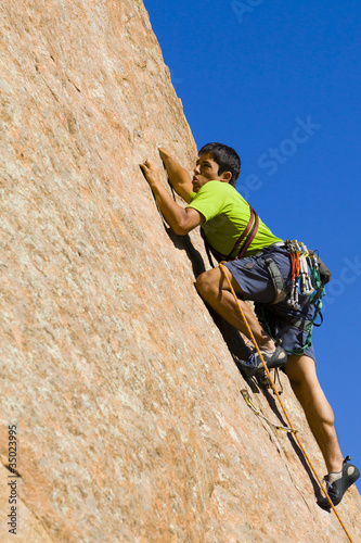Hispanic man rock climbing