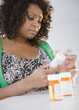African American woman looking at prescription bottles