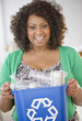 African American woman carrying recycling bin