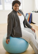 African American woman sitting on exercise ball