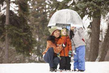 Chinese mother under umbrella with children