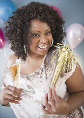 African American woman with noise maker and glass of Champagne