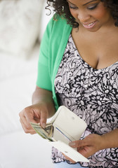 African American woman putting money in her wallet