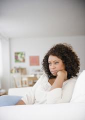 Sad African American woman sitting on sofa