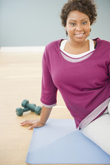 African woman sitting on yoga mat with dumbbells