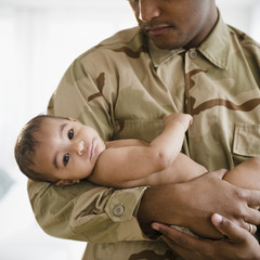 Solder in uniform holding baby boy