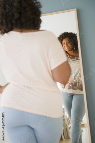 African American woman looking at reflection in mirror