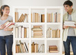 Couple with books standing near bookshelf