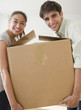 Couple carrying cardboard box together
