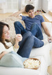 Couple eating popcorn and watching television