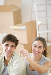 Excited couple holding keys to new home