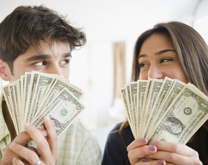 Couple holding handfuls of money