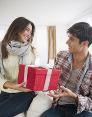 Woman handing husband Christmas gift