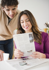 Couple looking at newspaper together