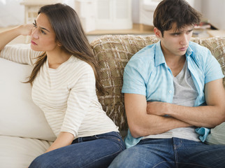 Angry couple sitting on sofa together