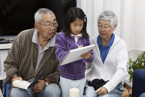 Asian grandparents watching granddaughter drawing