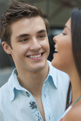 Hispanic man watching laughing girlfriend