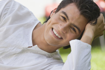 Smiling Hispanic man laying on ground