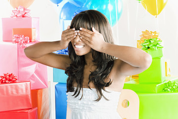 African American woman with eyes covered next to birthday presents