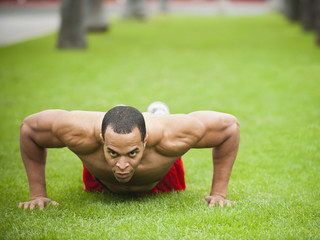 Mixed race man doing push-ups in park
