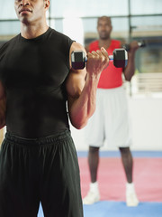 Men exercising with hand weights in health club