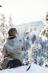 Caucasian woman snowshoeing in remote area taking photographs