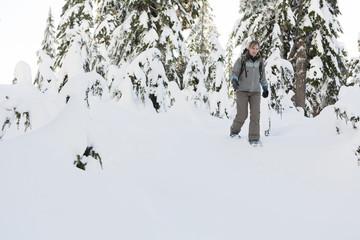 Caucasian woman snowshoeing in snow