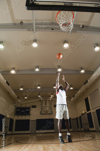 Black man shooting basketball on basketball court