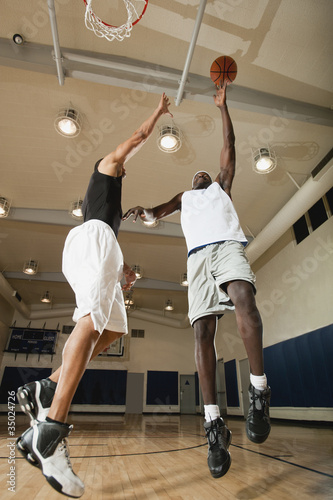 Men playing basketball on basketball court
