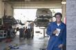 Mixed race mechanic taking break in auto repair shop