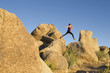 Hispanic woman jumping from rock to rock