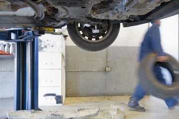 Mixed race mechanic carrying tire in auto repair shop