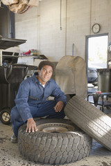 Mixed race mechanic checking tire in auto repair shop