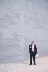 Hispanic businessman standing on sidewalk with hard-hat