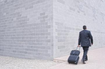 Hispanic businessman pulling luggage on sidewalk