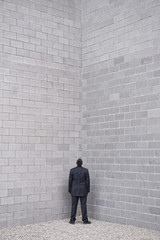 Hispanic businessman standing in corner